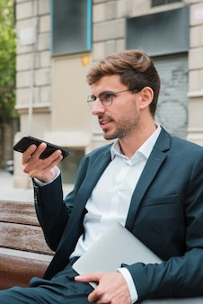 Close-up of a man sitting on bench talking on the phone with the digital voice assistant