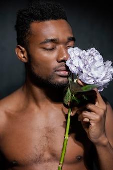 美しい花の香りのクローズアップ男