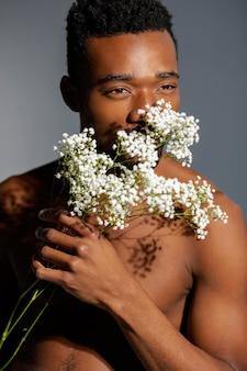 花の匂いを嗅ぐクローズアップ男