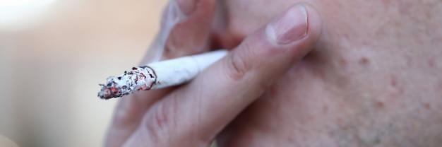 Close up man smoking cigarette, addictive habit