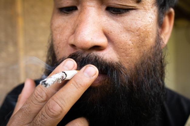 Close up of man smoking cigarette.