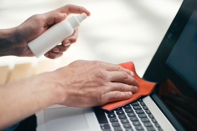 Закройте вверх. человек распыляет спрей на поверхность ноутбука. концепция охраны здоровья