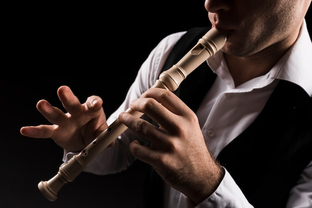 Close-up man on stage playing the flute
