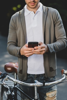 Close-up of man standing with bicycle using mobile phone