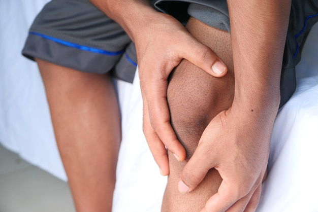Close up on man suffering knee joint pain