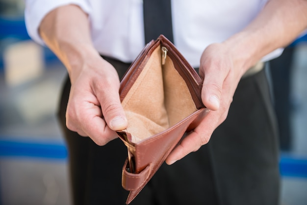 Close-up of man in suit holding empty purse.