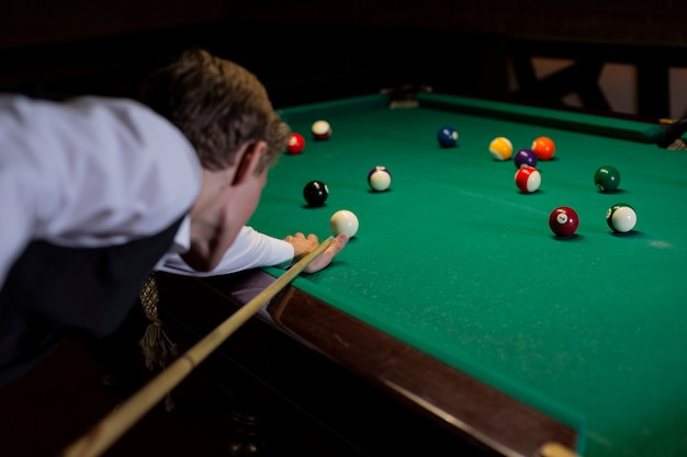 Close-up man in suit playing billiard