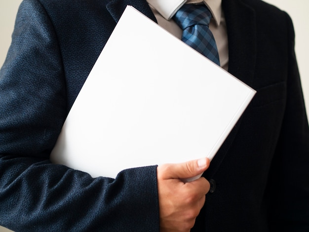 Close-up man in suit with notebook mock-up