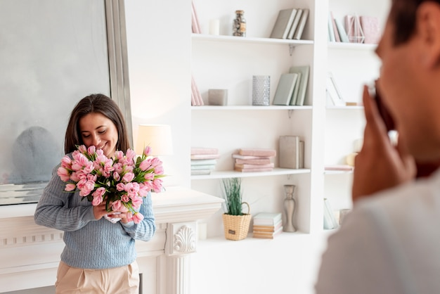 Close-up man surprising woman with flowers