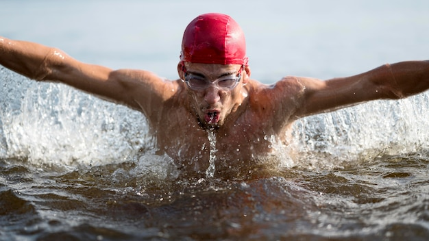 Uomo del primo piano che nuota nel lago