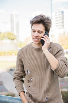 Close-up of a man talking on phone outdoors