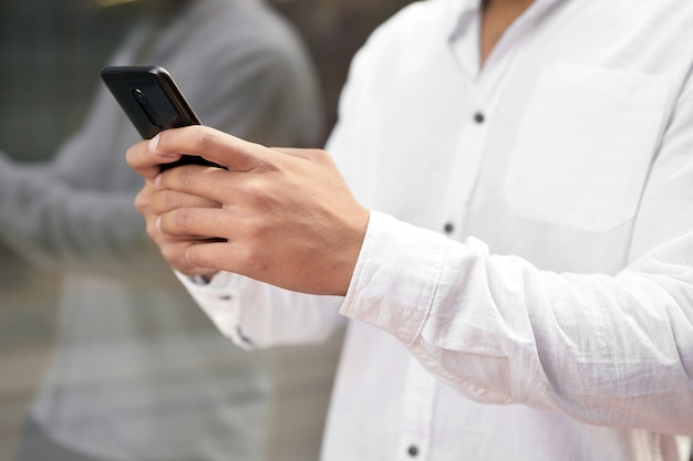 Close up man texting on cell phone