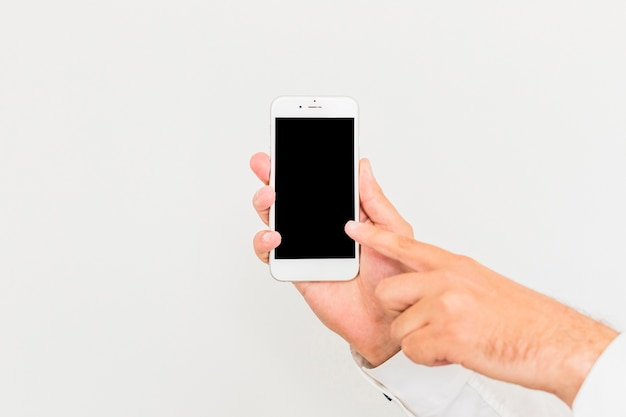 Close-up of a man touching smartphone screen against white background