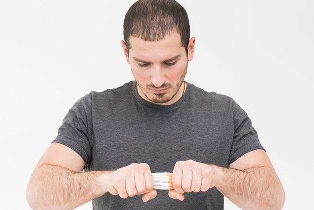 Close-up of a man trying to break the pile of cigarette with hands isolated on white background
