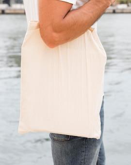 Крупный план мужчина с помощью перерабатываемой хозяйственной сумки