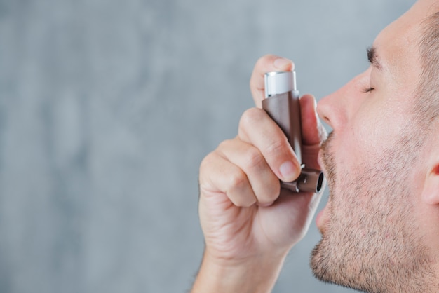 Close-up of a man using asthma inhaler against blur backdrop