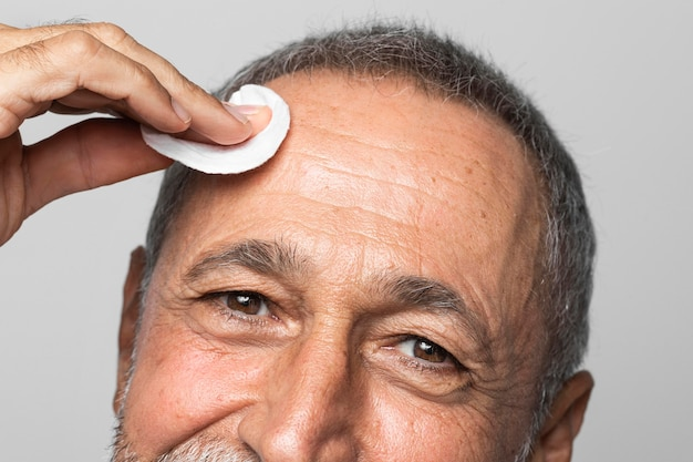 Close-up man using cotton pad on forehead