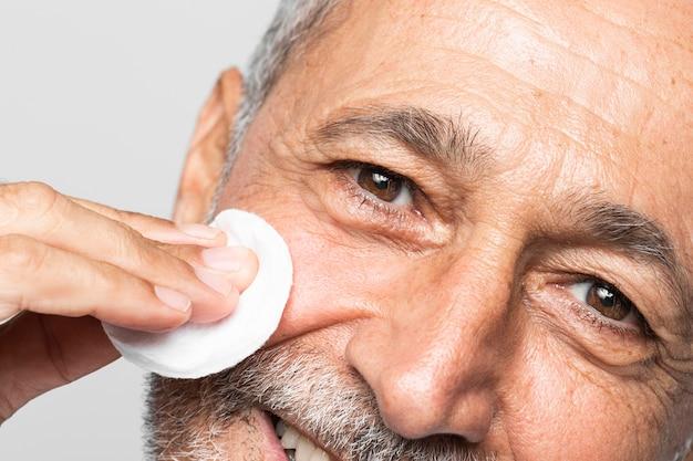 Close-up man using cotton pad