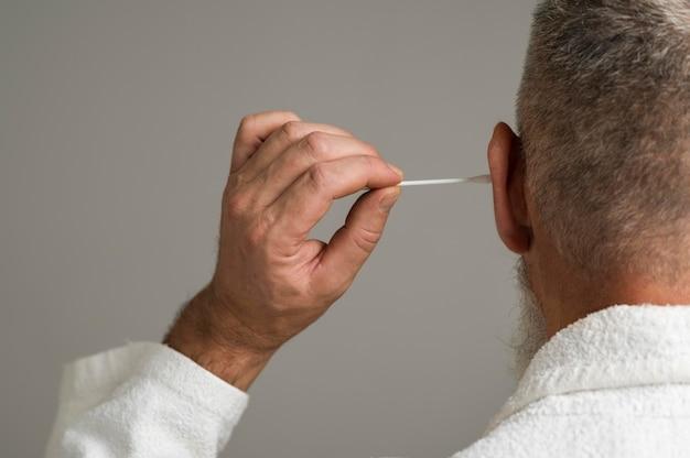 Primo piano uomo che usa un batuffolo di cotone