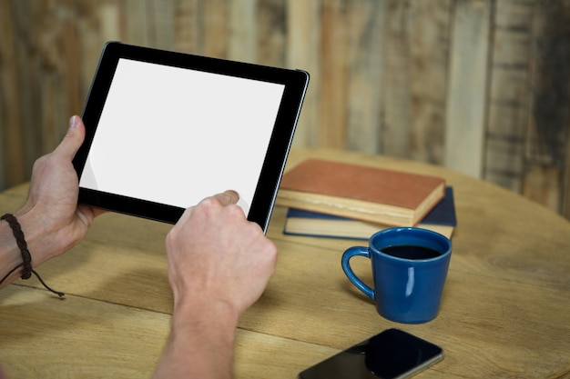 Close-up of man using digital tablet with blank screen in coffee shop