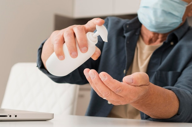 Close-up man using disinfectant