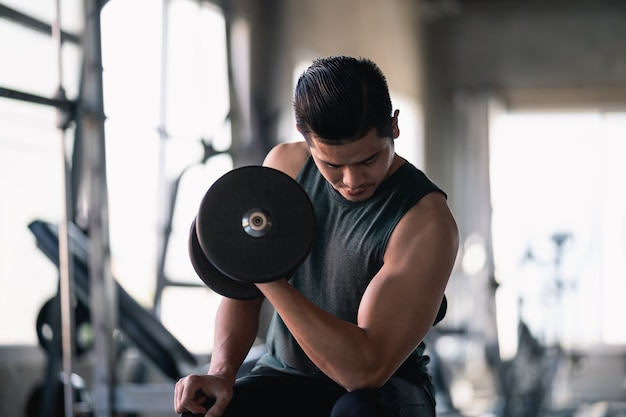 Close up of man using dumbbell exercise at gym