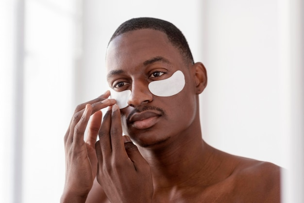 Close up man using eye patches