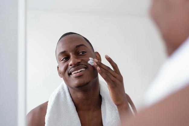 Close up man using face cream