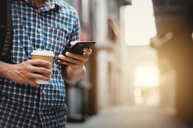 Close up of man using his mobile phone and cup of a coffee on the street. shopping and travel concept.