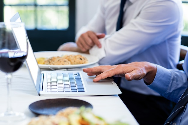 Close-up of man using laptop during a business lunch meeting