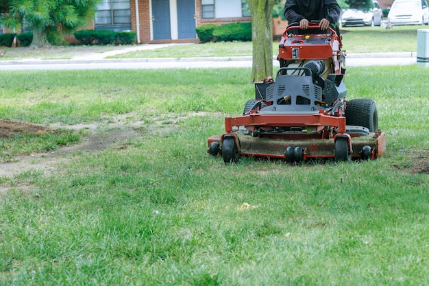 Close up of man using a lawn mower a gardener cutting grass by lawn mower