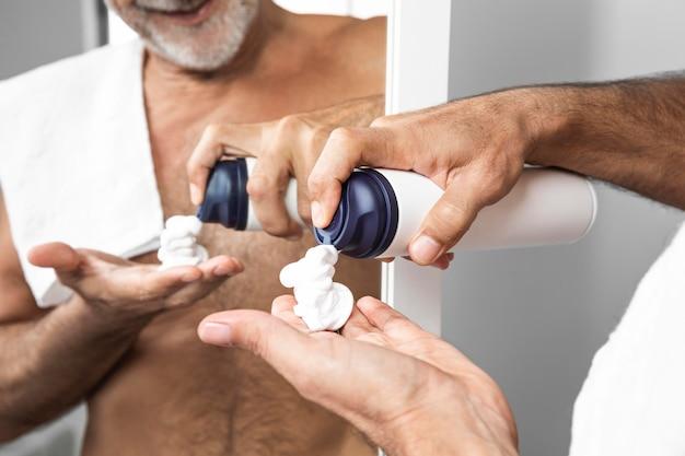 Close-up man using shaving cream