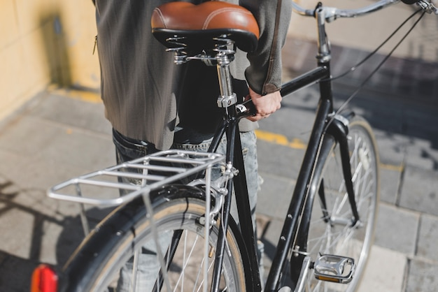Close-up of man walking with bicycle on staircase