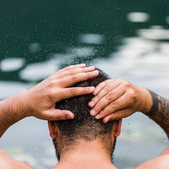 Close-up of man washing his head with lake water