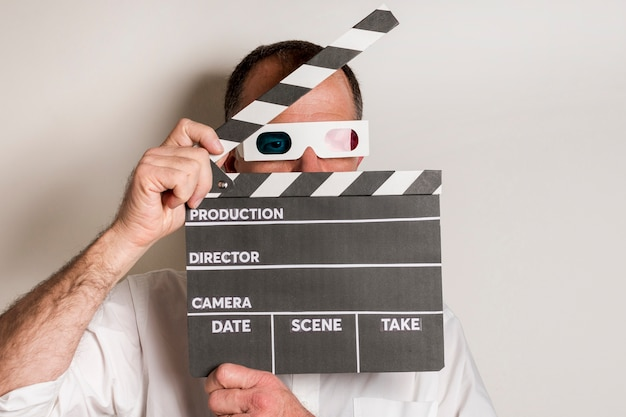 Close-up of a man wearing 3d glasses holding clapperboard against white backdrop