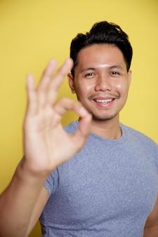 黄色の壁に隔離された彼の手でokサインを示すカジュアルなtシャツを着ている男性をクローズアップ