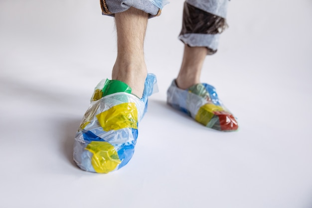 Close up of man wearing plastic on white wall. male model in shoes made of garbage. fashion, style, recycling, eco and environmental concept. too much pollution, we're eating and taking it.