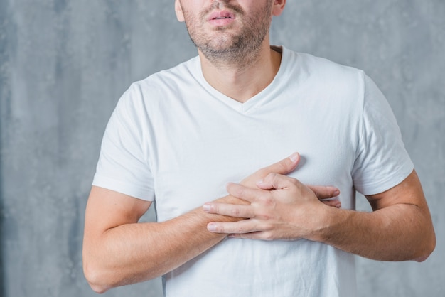 Close-up of a man in white t-shirt having heart pain