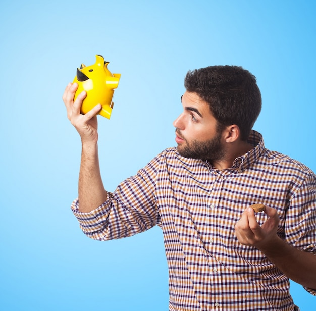 Close-up of man, who looking in piggy bank
