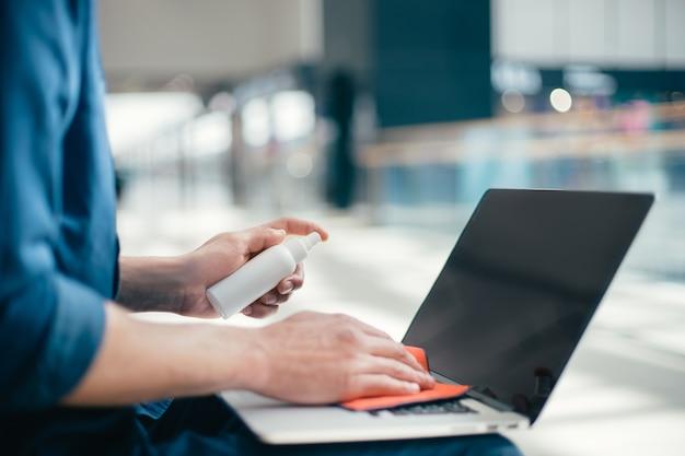 Закройте вверх. человек, вытирая пыль с клавиатуры ноутбука.
