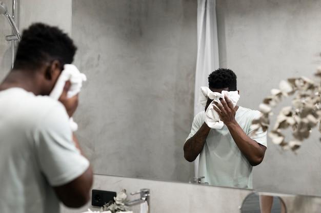 Close up man wiping his face