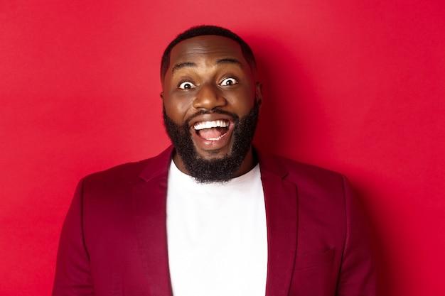 Primo piano dell'uomo con la barba fissando stupito la telecamera, sorridendo e guardando eccitato