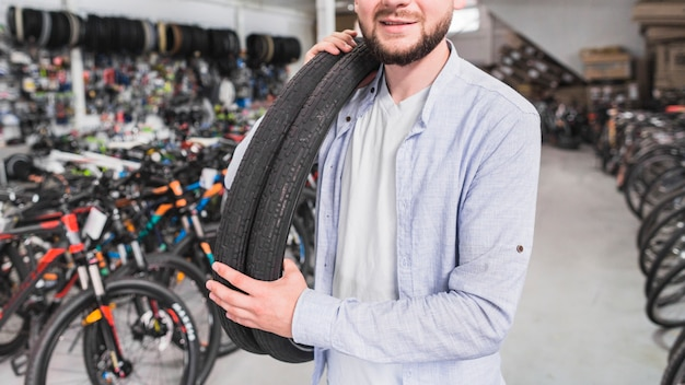 Close-up of a man with bicycle tires in shop