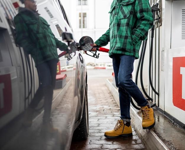 Close up uomo con auto alla stazione di servizio Foto Gratuite