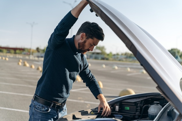 Close up of man with a car problem. confused man in a casual closes examines the car engine while standing at the road. stock photo