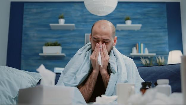 Primo piano di un uomo con raffreddore e influenza che soffia naso che cola