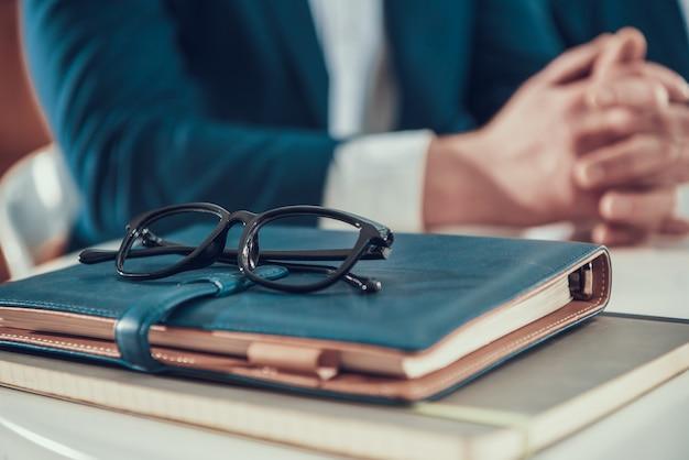 メガネとオフィスでノートを持つ男を閉じます。
