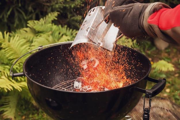 Крупным планом человек с перчатками дымоход стартер барбекю гриль