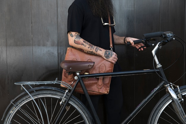 Close-up of a man with his bag and bicycle in front of black wall