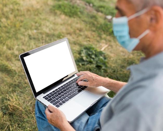 Uomo del primo piano con il computer portatile e la maschera